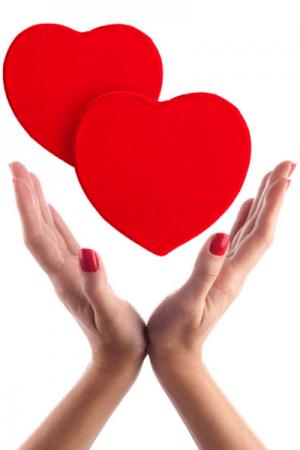 Handen met roodgelakte nagels ondersteunen 2 harten